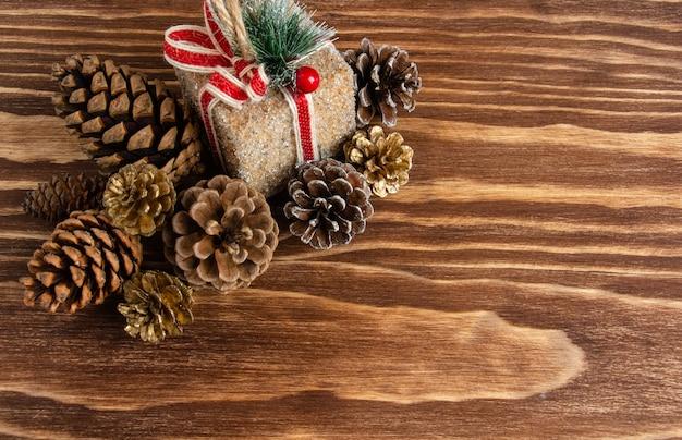 작은 선물과 나무 배경에 있는 많은 숲 콘, 아름다운 크리스마스와 새해 12월...