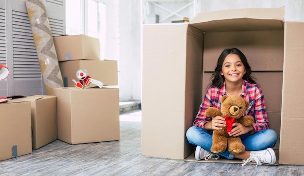 테디베어를 안고 있는 어린 소녀가 판지 상자에 숨어 있고 아마도 넓은 아파트에서 부모님과 숨바꼭질을 하고 있을 것입니다