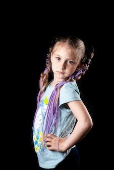 보라색 아프리카 탄성 밴드가있는 검은 색 바탕에 작은 소녀, 탄성 밴드의 땋은 머리는 두 개의 꼬리를 멋지게 묶었습니다.