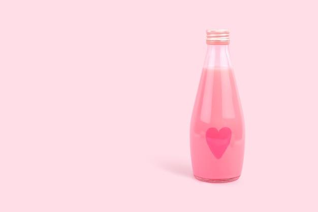 Маленькая стеклянная бутылка с нарисованным на ней сердечком и розовый молочный напиток