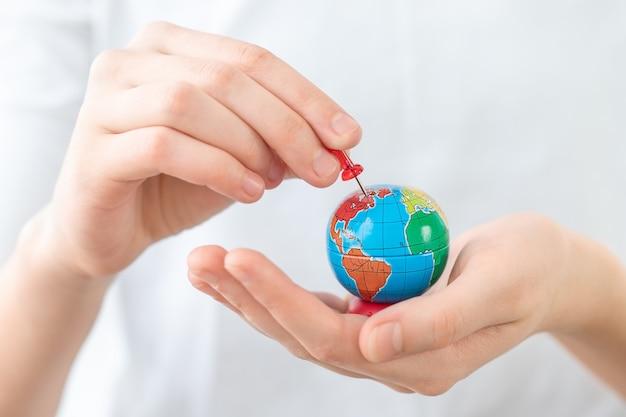 旅行のために選択された場所を指す手に小さな地球儀