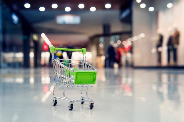 대형 쇼핑몰에 있는 작은 녹색 장난감 카트. 슈퍼마켓에서 쇼핑 및 판매의 개념. 슈퍼마켓에서 쇼핑 카트를 흐리게 합니다.