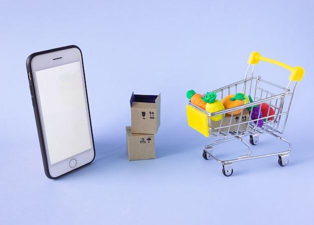 과일, 상자, 전화기가 들어있는 작은 식료품 카트
