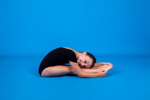 Маленькая гимнастка в черном купальнике выполняет разминку на синем фоне с местом для текста
