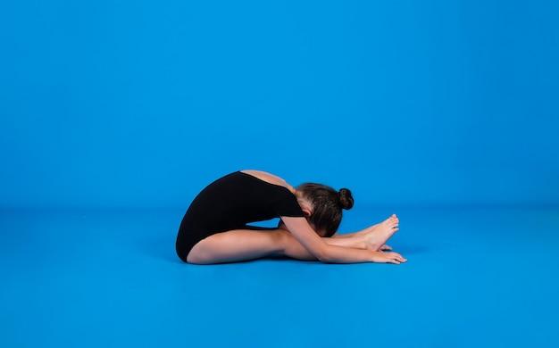 Маленькая гимнастка в черном купальнике выполняет упражнения на пластику на синем фоне с местом для текста