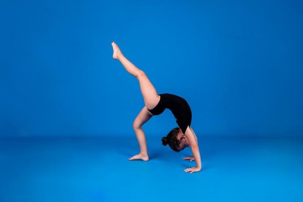 Маленькая гимнастка в черном купальнике стоит на руках на синем фоне с местом для текста