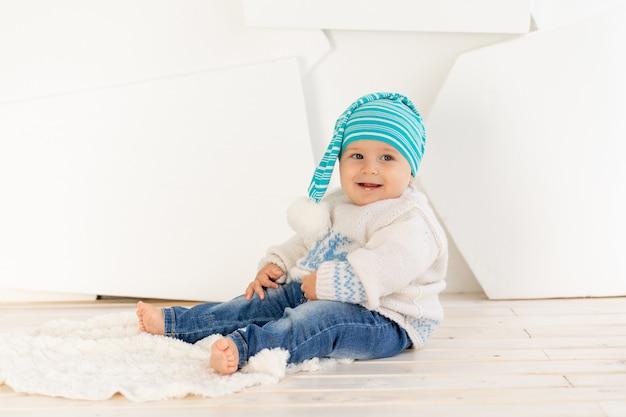 니트 따뜻한 재킷과 모자에 6 개월 된 작은 행복한 아이가 집에 밝은 방의 깔개에 앉아있다