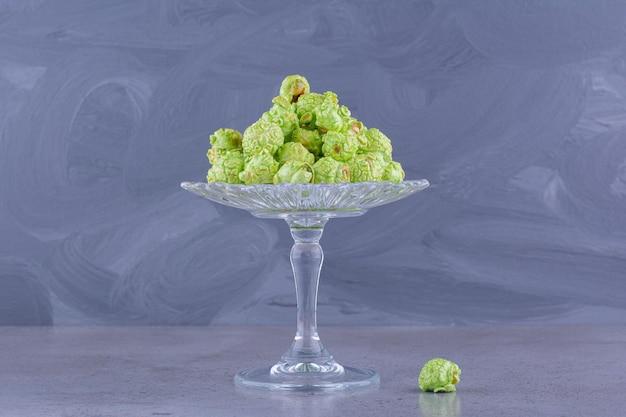 Небольшая куча зеленого засахаренного попкорна на стеклянной подставке для конфет на мраморном фоне. фото высокого качества