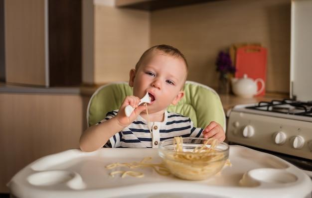 Маленький голодный мальчик в полосатой футболке сидит на высоком стуле и ест макароны в прозрачной тарелке.