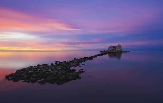 여러 색으로 칠해진 하늘 아래 바다 한가운데있는 작은 섬