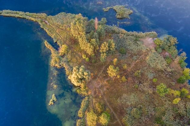 Небольшой островок на озере с желтыми осенними деревьями.