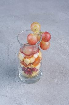 Небольшая банка, наполненная различными нарезанными фруктами на мраморном фоне.