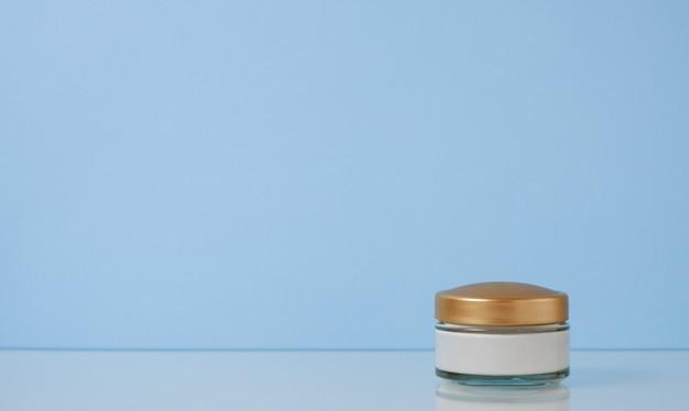 Маленькая баночка крема с бежевой крышкой