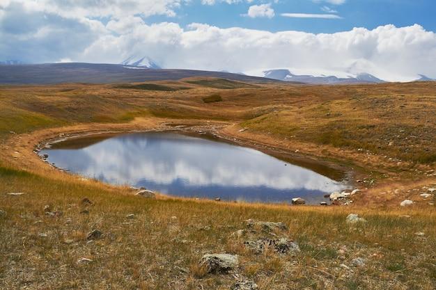 Небольшое озеро в степи, водопад среди гор. плато укок на алтае. сказочные холодные пейзажи. кто-нибудь вокруг