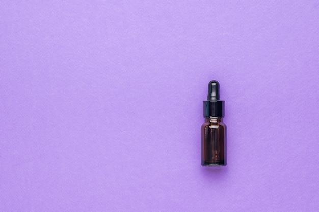 Небольшой медицинский флакон с пипеткой на фиолетовом фоне. концепция лечения и ухода за телом с помощью натуральных средств. плоская планировка.