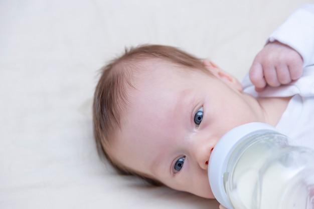 Маленький новорожденный мальчик пьет молоко из бутылочки с соской.