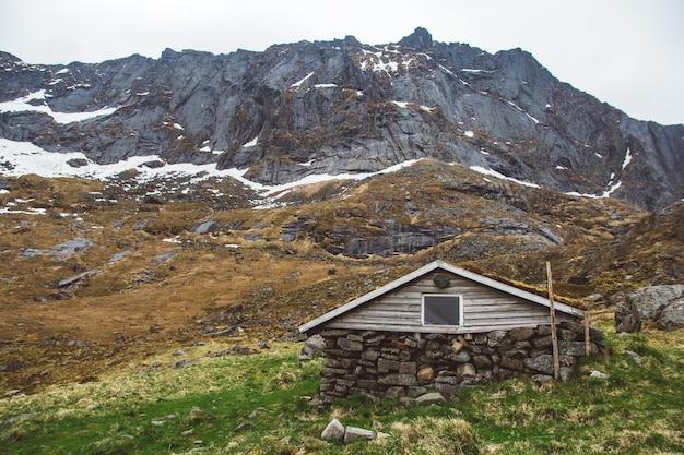 山の背景に苔で覆われた小さな古い石と木の家。