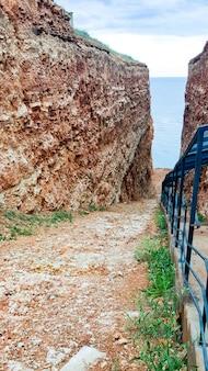 険しい崖の間の小さな通路。高い石の崖と崖沿いの階段の間のビーチの眺め