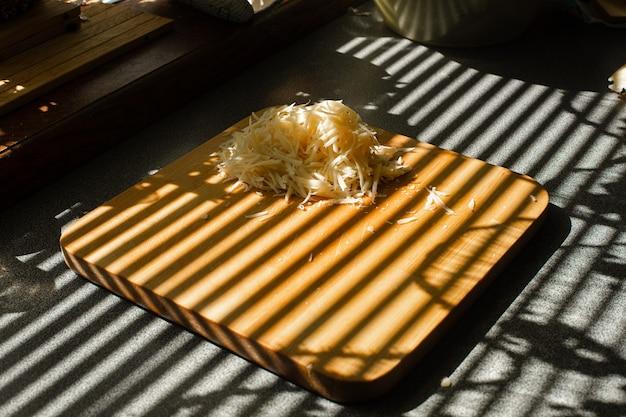 강판된 신선한 치즈의 작은 더미는 부엌에 있는 나무 판자에 놓여 있습니다