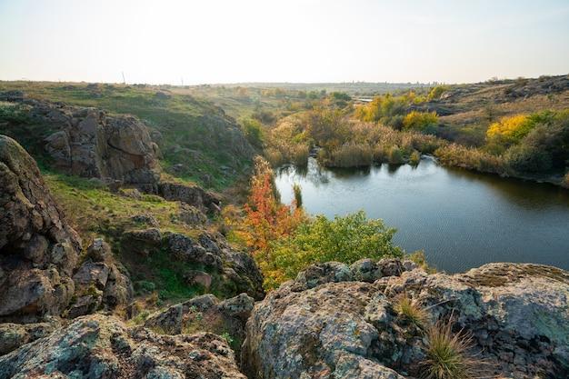 환상적으로 아름다운 푸른 하늘을 배경으로 넓은 녹황색 들판에 있는 작은 오래된 돌 더미
