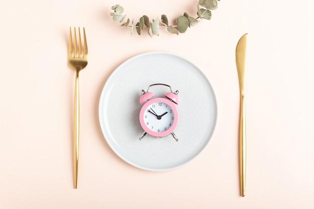 최소한의 접시에 있는 작은 분홍색 알람 시계, 황금색 포크와 나이프, 분홍색 배경에 유칼립투스 장식