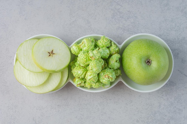 Небольшое блюдо с яблоками и конфетами для попкорна на мраморной поверхности