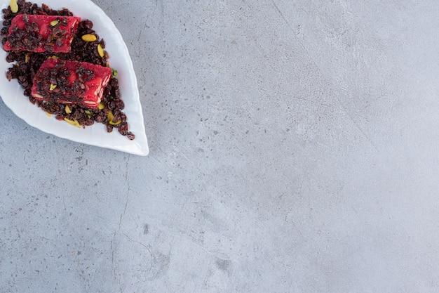 Небольшое блюдо с ароматными и цветными рахат-лукумами на мраморном фоне.