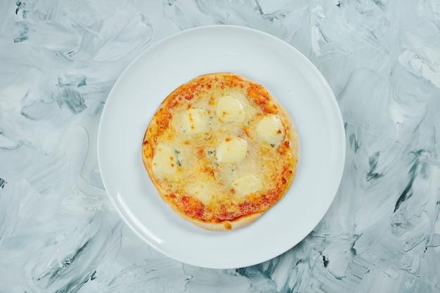 Небольшая порция детской пиццы 4 сыра с моцареллой и голубым сыром с плесенью на белой тарелке на сером столе