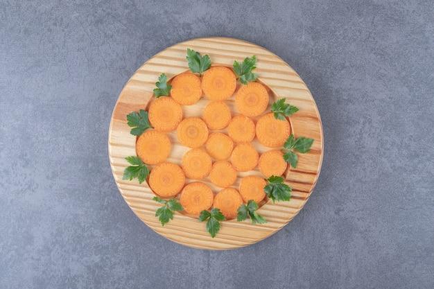 Небольшая порция нарезанной моркови и зелени на мраморной поверхности.