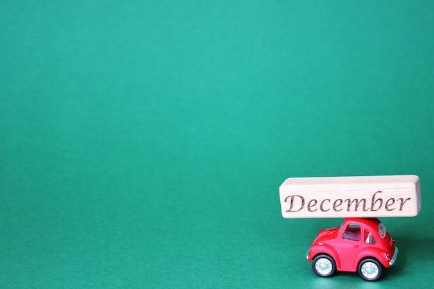 Маленькая красная игрушечная машинка с деревянным блоком с надписью «декабрь» на крыше. зеленый фон. приближаются рождественские и новогодние праздники.