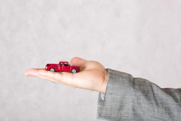사업가의 손에 있는 작은 빨간 장난감 자동차. 확대. 텍스트를 위한 여유 공간입니다.