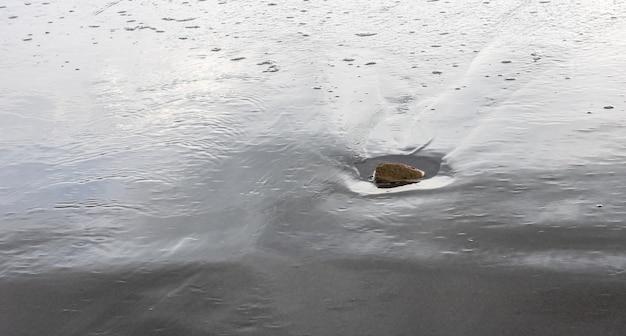 바다 해변의 모래 땅에 작은 바위