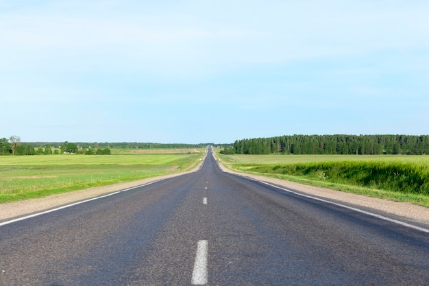 Небольшая сельская асфальтированная дорога. пейзаж с голубым небом, травой и деревьями. по проезжей части движутся машины