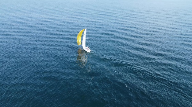 黄色と白の帆を備えた小さな帆船が青い海を航行します。海の観光と夏休み