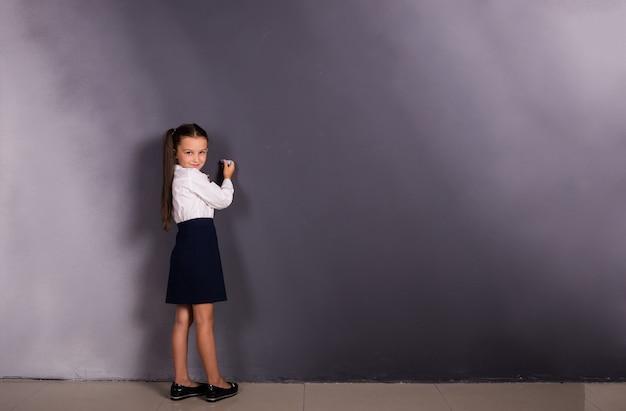 Маленькая школьница в форме стоит у доски с местом для текста