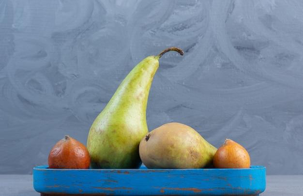 大理石の背景の青い大皿に梨の小さなサービング。
