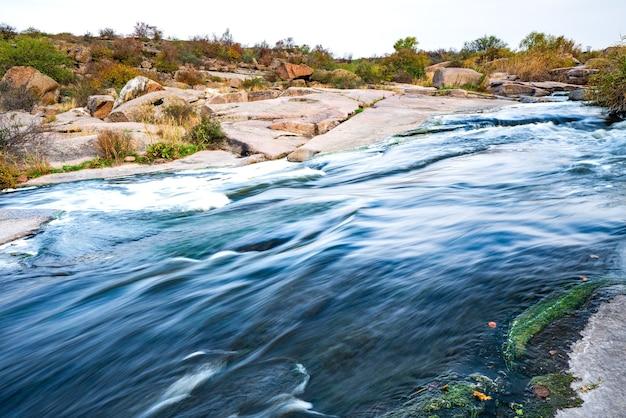 Небольшой сияющий ручей протекает среди гладких влажных и темных камней и сухих невысоких деревьев.
