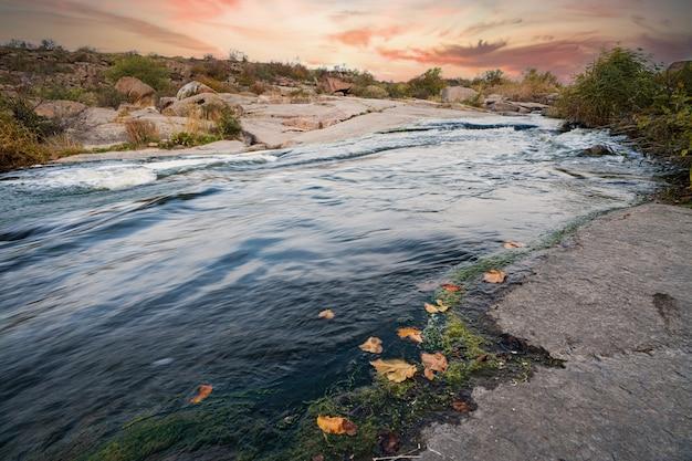 Небольшой сияющий ручей протекает среди гладких влажных и темных камней.