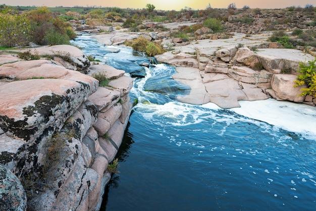 부드럽고 젖은 검은 돌들 사이로 반짝이는 작은 물줄기가 흐른다