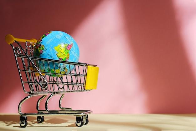 Маленькая тележка для покупок в супермаркете с игрушечной планетой. концепция мирового потребления, покупок в магазине, продаж