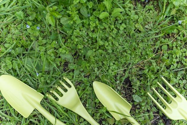 В саду на зеленой траве подряд лежат лопатка и грабли. устройства для обработки земли, с целью посадки растений. инструменты, декоративные инструменты. обработка земли.
