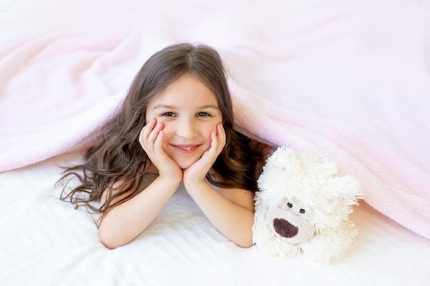 Маленькая улыбающаяся девочка 5-6 лет лежит в постели с мишкой тедди, положив руки под щеки