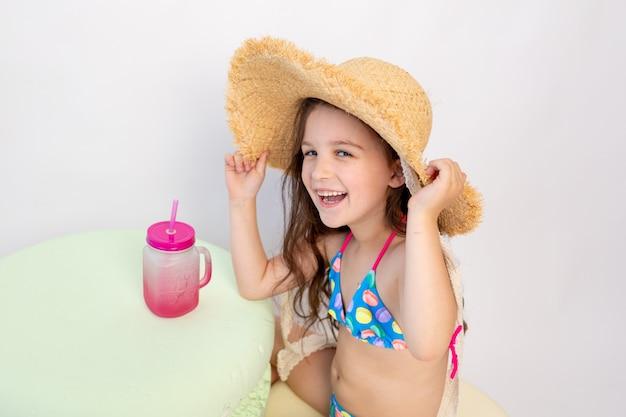 小さな笑顔の女の子は水着と白のカクテルと帽子に座っています。