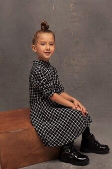 スタジオの暗い背景に小さな笑顔の女の子。子供はモデルです。幸せな子供時代。