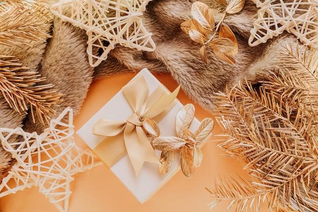 弓のクローズアップ付きの小さな正方形のギフト。近くには格子縞の金色のクリスマスツリーの枝、お祝いの星の装飾があります。新年、クリスマス、家の快適さのためのコンセプト。パステルカラー。