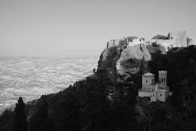 森の丘の上の小さな石造りの家を黒と白で撮影