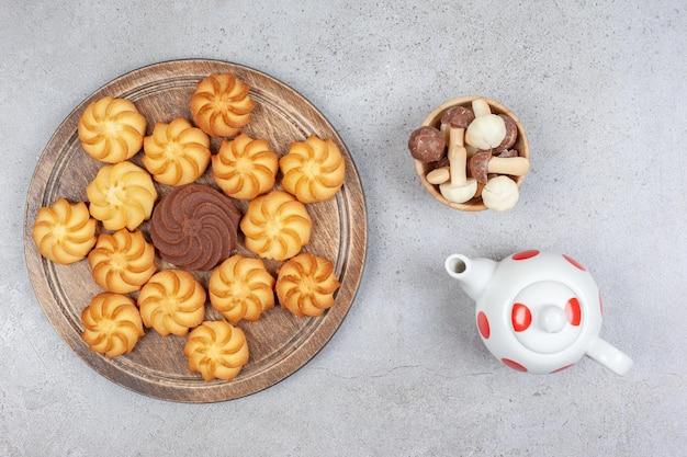 Небольшой чайник, миска с шоколадными грибами и деревянная доска печенья на мраморном фоне. фото высокого качества