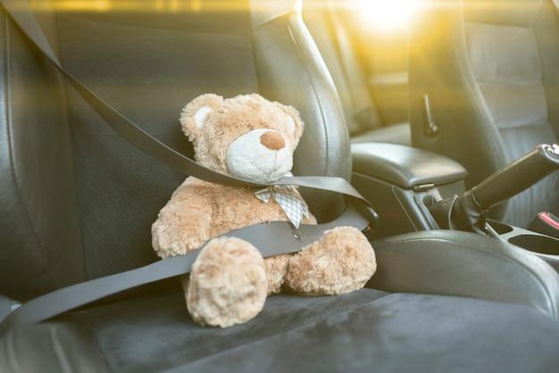 車の安全ベルトで保護された小さなテディベア、車両事故のセキュリティ