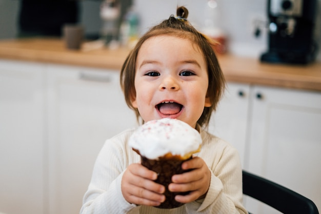 Маленькая малышка ест кулич на православную пасху Premium Фотографии
