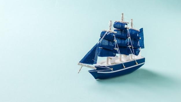 밝은 파란색 배경에 작은 장난감 범선. 여행과 모험의 개념.